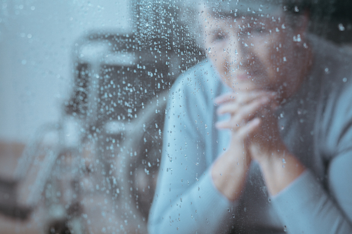 Elder lady with depression sitting alone in the room, looking outside while it is raining, wondering why is my pain worse when it rains?