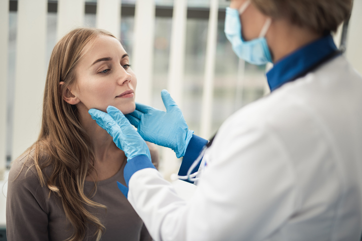 Concept of professional consultation in therapist system. Close up portrait of doctor woman examining tonsils of smiling young lady in medical office.