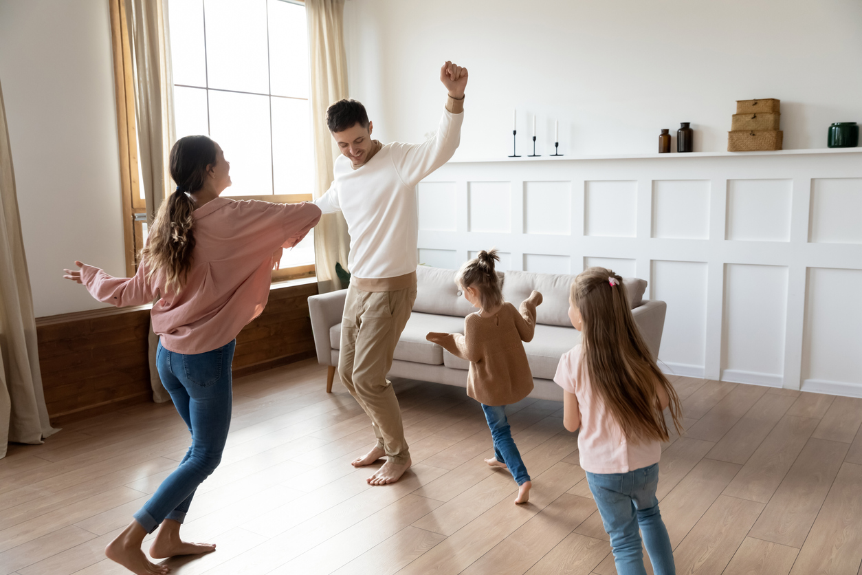Funny active family of four young adult parents and cute small children daughters dancing together in living room interior, carefree little kids with mum dad having fun laughing enjoy leisure at home, showing How Can You Keep Your Family Active When Team Sports Are On Hold.