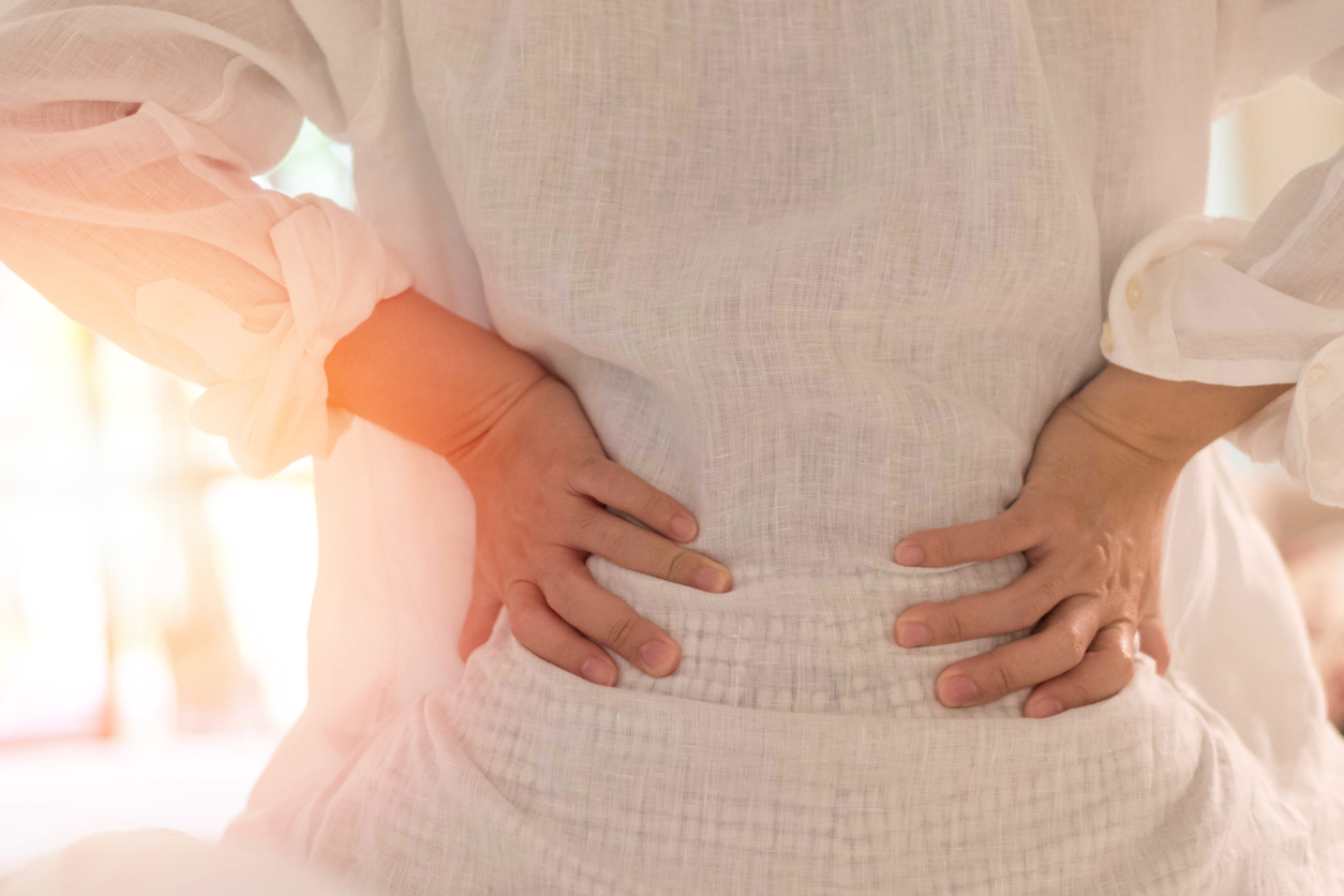 Back pain in woman concept. Female patient hurt from lower backache from bowel and bladder problems, palvic inflammatory disease (PID) or motherhood pregnancy.