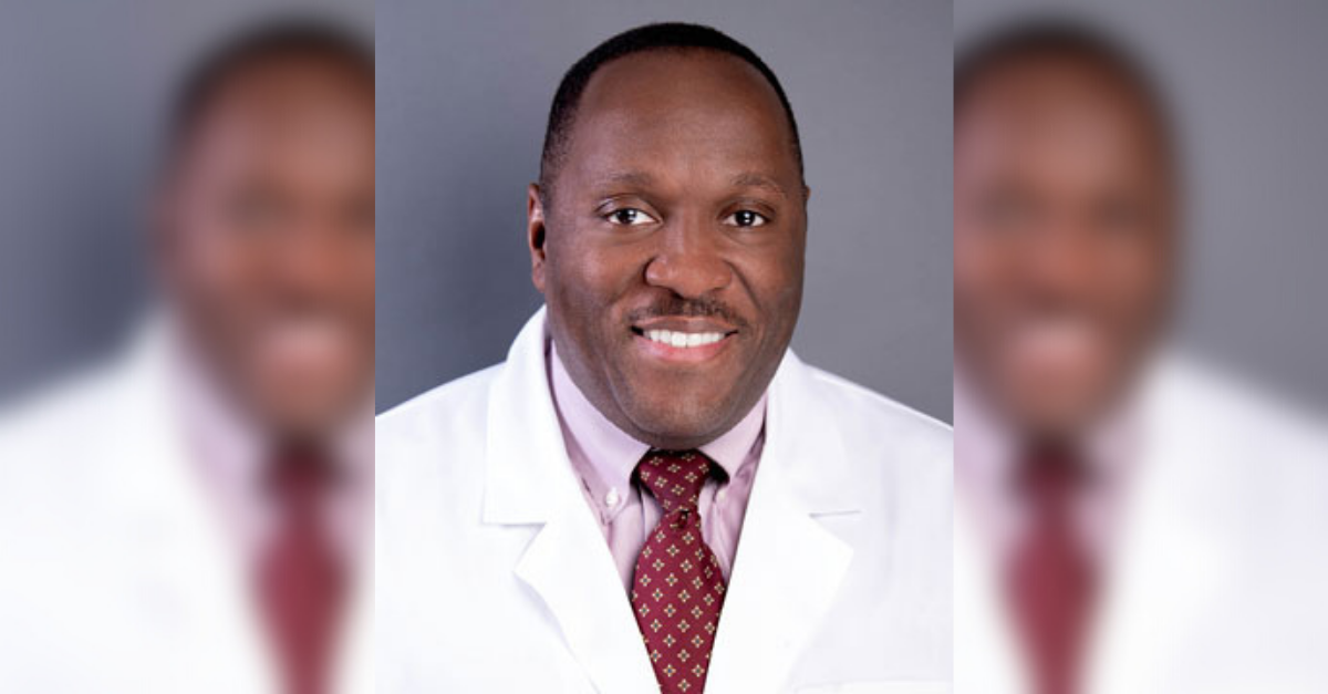 Dr. Daryl Sherrod is wearing a white coat, pink button down shirt and a red tie. He is smiling.